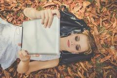 La muchacha es relajante con la tableta digital al aire libre Imagen de archivo