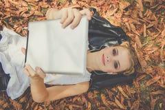 La muchacha es relajante con la tableta digital al aire libre Imágenes de archivo libres de regalías