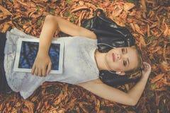 La muchacha es relajante con la tableta digital al aire libre Imagenes de archivo