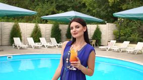 La muchacha es relajante con un cóctel por la piscina