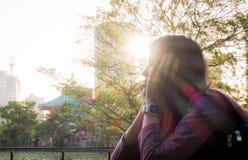 La muchacha es relajante en parque con el sol que brilla en su efecto de la silueta de la cara Fotografía de archivo