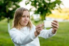 La muchacha es un adolescente En el verano en parque en naturaleza En sus manos sostiene un smartphone Fotografía el paisaje Imagen de archivo libre de regalías