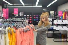La muchacha escoge un nuevo vestido en la tienda Fotografía de archivo libre de regalías