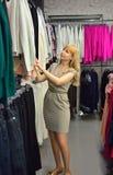 La muchacha escoge un nuevo vestido en la tienda Imágenes de archivo libres de regalías