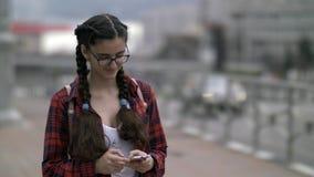 La muchacha escribe algo en el teléfono, charla en Internet, correspondencia imagen de archivo libre de regalías