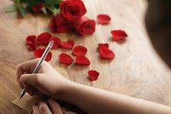 La muchacha escribe algo en una tarjeta de papel en viejo fondo de madera Fotografía de archivo libre de regalías
