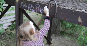 La muchacha escribe con tiza en el hierro almacen de metraje de vídeo