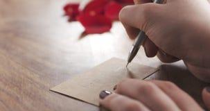 La muchacha escribe día de madres en una tarjeta de papel en viejo fondo de madera Imagenes de archivo
