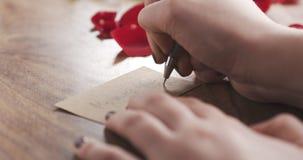 La muchacha escribe día de madres en una tarjeta de papel en viejo fondo de madera Fotos de archivo
