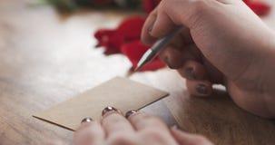 La muchacha escribe día de tarjetas del día de San Valentín en una tarjeta de papel en viejo fondo de madera Imágenes de archivo libres de regalías