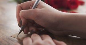 La muchacha escribe día de tarjetas del día de San Valentín en una tarjeta de papel en viejo fondo de madera Imagen de archivo