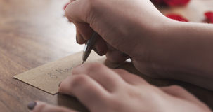 La muchacha escribe el 8 de marzo en una tarjeta de papel en viejo fondo de madera Foto de archivo libre de regalías