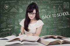 La muchacha escribe en el libro mientras que lee Fotos de archivo libres de regalías