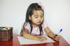 La muchacha escribe en el papel fotografía de archivo
