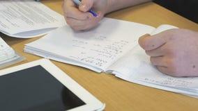 La muchacha escribe en un cuaderno de las matemáticas de la escuela almacen de metraje de vídeo