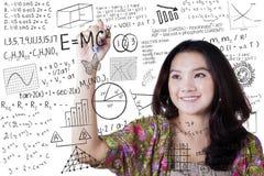 La muchacha escribe fórmula de la matemáticas y de la ciencia Imagen de archivo