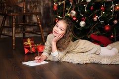 La muchacha escribe la letra a santa Imagenes de archivo