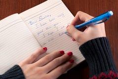 La muchacha escribe la letra a Santa Claus en el escritorio de madera imagen de archivo