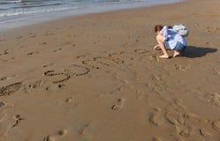 La muchacha escribe la palabra 'verano 'en la arena en la puesta del sol Ondas y huellas en el arena de mar fotos de archivo libres de regalías