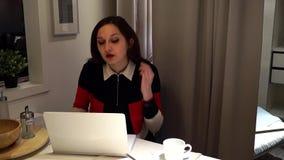 La muchacha escribe rápidamente los mensajes, texto en el ordenador portátil metrajes