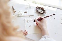 La muchacha escribe una letra a su hombre querido que se sienta en casa en el t fotografía de archivo