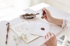 La muchacha escribe una letra a su hombre querido que se sienta en casa en el t fotografía de archivo libre de regalías