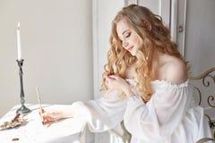 La muchacha escribe una letra a su hombre querido que se sienta en casa en la tabla en un vestido, una pureza y una inocencia de  imagen de archivo libre de regalías