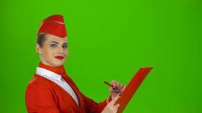 La muchacha escribe una pluma en una carpeta especial, ella es asistente de vuelo Pantalla verde Vista lateral almacen de video