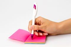 La muchacha escribe una pluma en un trozo de papel Imagen de archivo libre de regalías