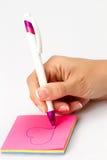 La muchacha escribe una pluma en un trozo de papel Fotos de archivo libres de regalías