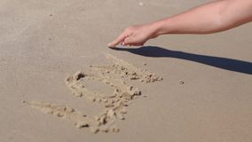 La muchacha escribió en el amor de la palabra de la arena almacen de video