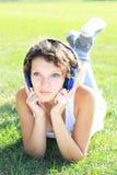 La muchacha escucha la música Foto de archivo