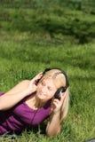 La muchacha escucha la música Imagenes de archivo