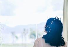La muchacha escucha la música con el auricular imagenes de archivo