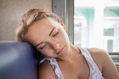 La muchacha escucha la música del tren Foto de archivo libre de regalías