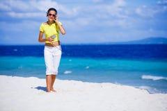 La muchacha escucha la música en la playa Imagen de archivo libre de regalías