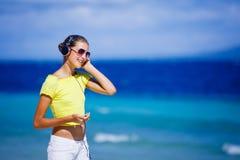 La muchacha escucha la música en la playa Foto de archivo