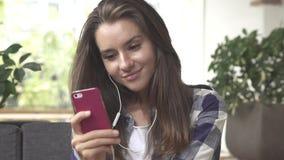La muchacha escucha la música en smartphone con los auriculares Fotos de archivo