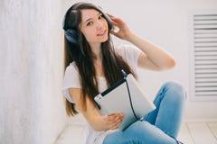 La muchacha escucha música que se sienta en el piso en el estudio Mientras que CRO (coordinadora) Foto de archivo libre de regalías