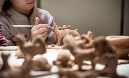 La muchacha esculpe de gatito de la arcilla Foto de archivo libre de regalías