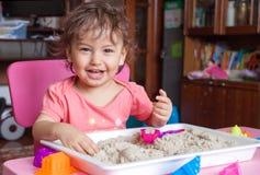 La muchacha esculpe fuera de la arena en su sitio Imágenes de archivo libres de regalías