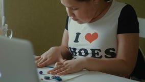 La muchacha esculpe las estatuillas del plasticine en la tabla foto de archivo