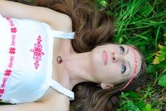 La muchacha eslava hermosa joven con el pelo largo y el traje étnico eslavo miente en la hierba en un bosque del verano Imagen de archivo