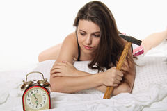 La muchacha espera el despertador con un martillo a disposición Imagenes de archivo