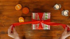 La muchacha está abriendo la caja de regalo de cumpleaños con la cinta roja, visión superior almacen de video