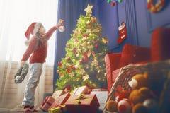 La muchacha está adornando el árbol de navidad Imagenes de archivo