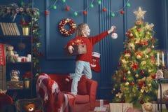 La muchacha está adornando el árbol de navidad Imagen de archivo libre de regalías