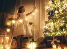 La muchacha está adornando el árbol de navidad Imágenes de archivo libres de regalías
