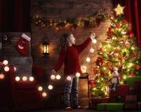 La muchacha está adornando el árbol de navidad Foto de archivo