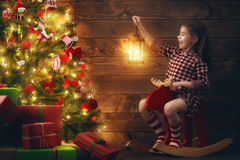 La muchacha está adornando el árbol de navidad Foto de archivo libre de regalías
